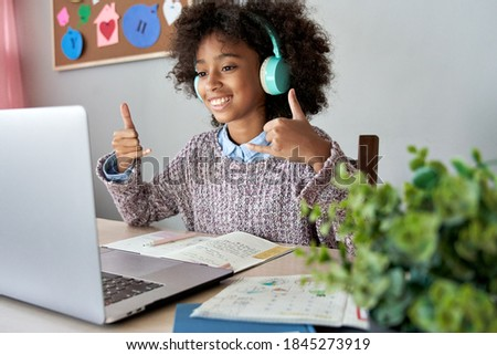 Smiling african mute dumb child school girl learning online class on laptop communicating with teacher by video conference call using sign language showing play hand gesture on virtual therapy lesson.