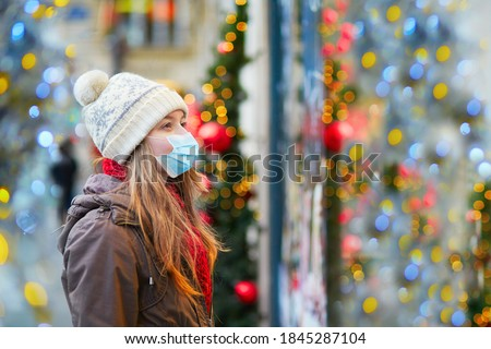 Girl wearing face mask on a Parisian street or at Christmas market looking at shop windows decorated for Christmas. Seasonal holidays during pandemic and coronavirus outbreak #1845287104