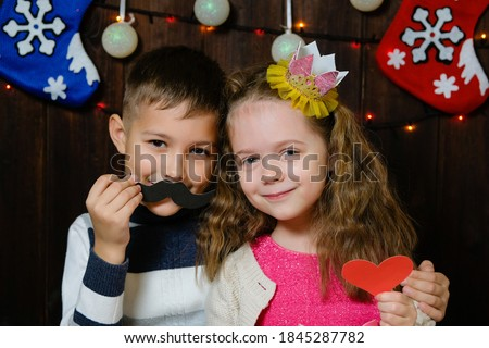 Kids with props for a photo booth. Little boy and girl with the requisite mustache, heart and crown on christmas wooden background. Event, holiday, party. Children congratulate happy new year.