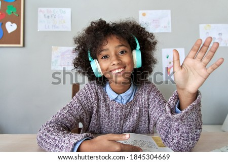 Happy african american kid child girl wearing headphones waving hand talking with remote teacher on social distance learning video conference call zoom class, headshot zoom portrait, web cam view. Royalty-Free Stock Photo #1845304669