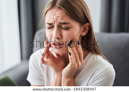 Toothache. Girl suffering from tooth pain and touching cheek while sitting on couch at home. Dental problem concept. Stock photo Royalty-Free Stock Photo #1845308947