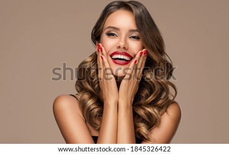Beautiful laughing brunette model  girl  with long curly  hair . Smiling  woman hairstyle wavy curls . Red  lips and  nails manicure .    Fashion , beauty and make up portrait Royalty-Free Stock Photo #1845326422