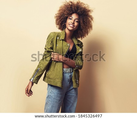 Fashionable young beautiful african american woman . Girl with afro hairstyle posing in leather jacket. Fashion, clothing and style. Royalty-Free Stock Photo #1845326497