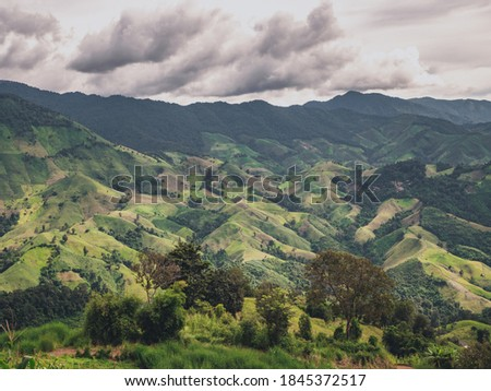 Beautiful green moutain with valley in rainy day background. Nature and landscape picture from Nan province, Thailand.