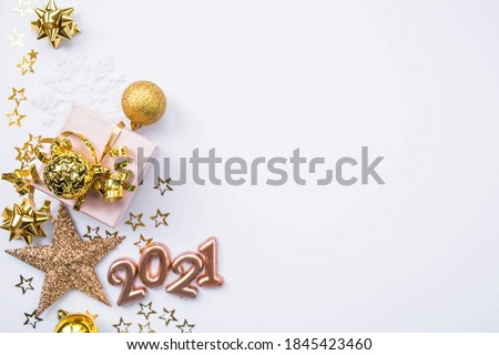 Christmas composition. Gifts, stars, gold jewelry and the number 2021 on a white background. Christmas, winter, new year concept. Flat lay, top view, copy space. Royalty-Free Stock Photo #1845423460