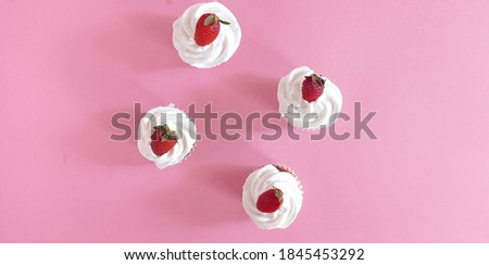 Photo of homemade cupcakes with strawberry as decorating. Vanilla cream cupcakes. Picture of baked at home cupcakes and pink background.