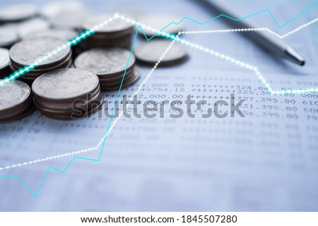 Plan save money 2021 concept. stock Charts on blur image of coins, bankbook, pen. for stock market digital analysis.