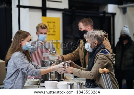 Volunteers serving hot soup for homeless in community charity donation center, coronavirus concept. Royalty-Free Stock Photo #1845553264