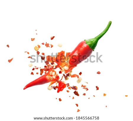 Chili flakes bursting out from red chili pepper over white background Royalty-Free Stock Photo #1845566758