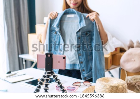 Young Asian woman entrepreneur review product and talking camera live recording video on social network at home. Online selling, business and technology concept. Royalty-Free Stock Photo #1845596386