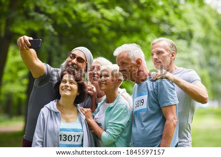 Group of happy senior friends taking part in summer marathon race standing together in forest park taking group selfie photo