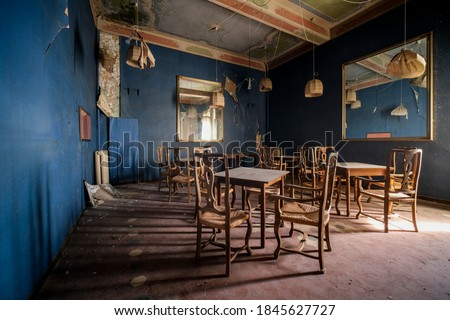 dining room with chairs and tables in abandoned restaurant bar. High quality photo Royalty-Free Stock Photo #1845627727