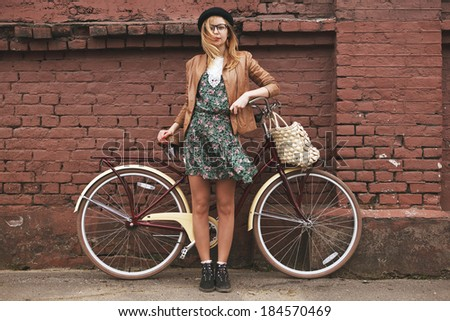 fashionable woman with vintage bike on brick wall background #184570469