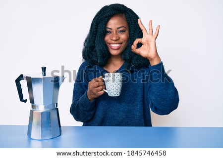 Beautiful african woman drinking a coffee from italian coffee maker doing ok sign with fingers, smiling friendly gesturing excellent symbol
