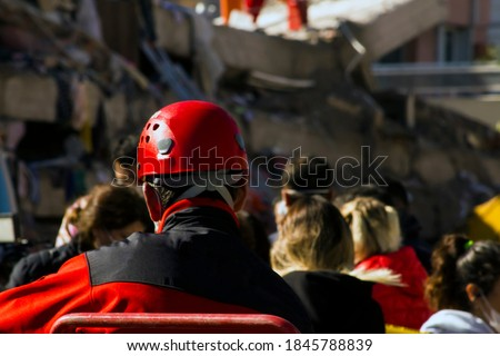 The back of the search and rescue worker blurred in front of the building destroyed in the earthquake,watching and resting Royalty-Free Stock Photo #1845788839