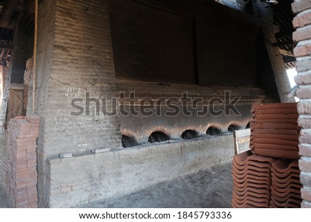 Traditional roofing tiles factory in the country side of Indonesia. Tiles made of clay are usually burned in a large furnace. Detail inside of high burning furnace built of red brick arrangement. #1845793336