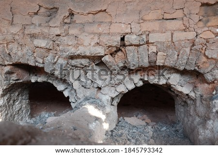 Traditional roofing tiles factory in the country side of Indonesia. Tiles made of clay are usually burned in a large furnace. Detail inside of high burning furnace built of red brick arrangement. #1845793342