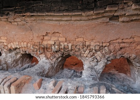 Traditional roofing tiles factory in the country side of Indonesia. Tiles made of clay are usually burned in a large furnace. Detail inside of high burning furnace built of red brick arrangement. #1845793366