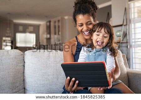 Young black mother and smiling daughter playing on digital tablet at home with copy space. Young african american woman with cheerful and excited little girl using digital tablet on couch at home.