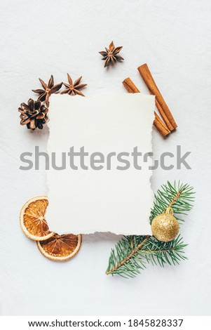 Greeting card for Christmas or New Yaer made of fir branche, spices and dried oranges and a cone with paper card note. Flat lay. Royalty-Free Stock Photo #1845828337