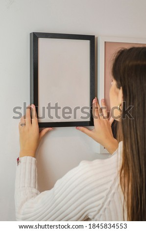 woman hanging black picture frame with white background Royalty-Free Stock Photo #1845834553