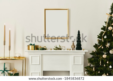 Christmas composition with gold mock up poster frame, white chimney and decoration. Christmas trees and wreath, candles, stars, light and elegant accessories. Template. Royalty-Free Stock Photo #1845836872