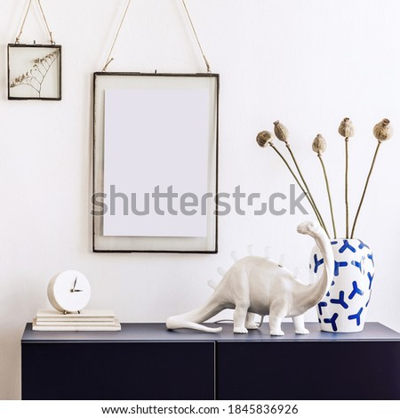 Stylish living room interior with mock up poster frames, navy blue commode, book, decoration and elegant personal accessories in modern home decor.  White wall. Template.