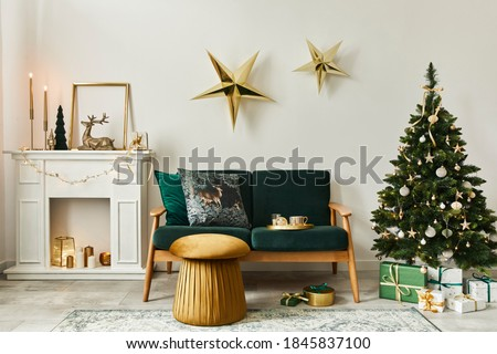 Stylish christmas living room interior with green sofa, white chimney, christmas tree and wreath, stars, gifts and decoration. Family time. Template. Royalty-Free Stock Photo #1845837100