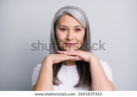 Photo portrait of elder beautiful woman with grey hair keeping hands near chin smiling isolated on grey color background