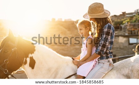 Happy family mother and daughter having fun riding horse inside ranch Royalty-Free Stock Photo #1845858685