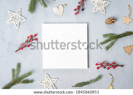 White blank canvas board and Christmas decoration on grey canvas backdrop. Top view. Mockup poster, Christmas concept. Royalty-Free Stock Photo #1845860851