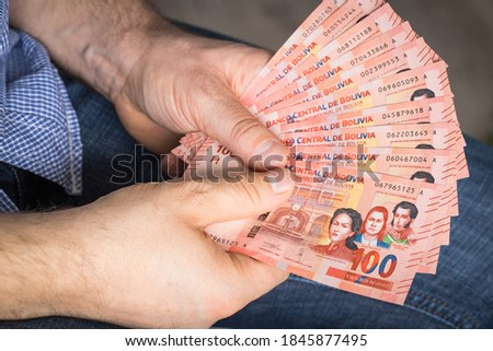 A large amount of Bolivian money kept in the hands Royalty-Free Stock Photo #1845877495