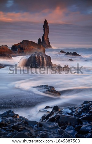 Majestic rocky needles from sea, Reynisdrangar, close to Vik Iceland. Dramatic sunset sky and with long exposure motion blurred waves. Royalty-Free Stock Photo #1845887503