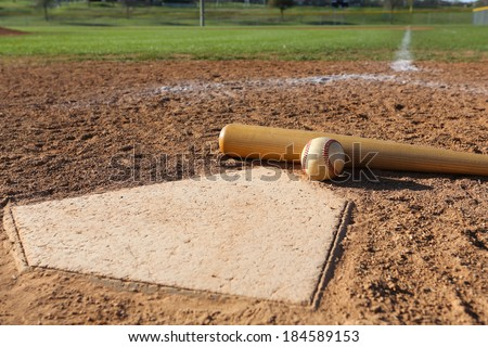 Baseball and Bat at Home Plate with the Field Beyond Royalty-Free Stock Photo #184589153