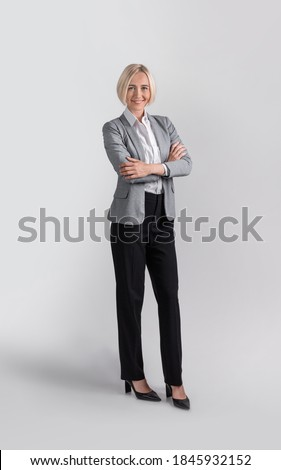 Full length portrait of positive female entrepreneur in formal clothes over light grey studio background. Beautiful businesswoman standing with crossed arms and smiling Royalty-Free Stock Photo #1845932152