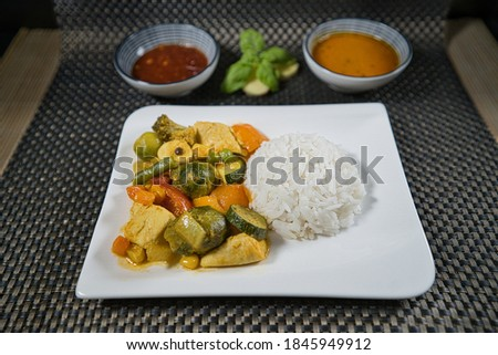 A portion of yellow rice curry with chicken and fresh organic vegetables on a white plate, product picture with curry sauce, chili dip, ginger and basil