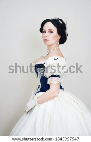 A beautiful elegant dark haired woman in a historic 1867 coronation dress on a white background looks at the camera Royalty-Free Stock Photo #1845957547