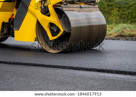Asphalt road roller with heavy vibration roller compactor press new hot asphalt on the roadway on a road construction site. Heavy Vibration roller at asphalt pavement working. Repairing. Royalty-Free Stock Photo #1846017913