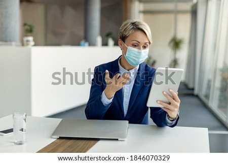 Female entrepreneur using digital tablet while having conference call and wearing protective face mask due to coronavirus pandemic.  Royalty-Free Stock Photo #1846070329