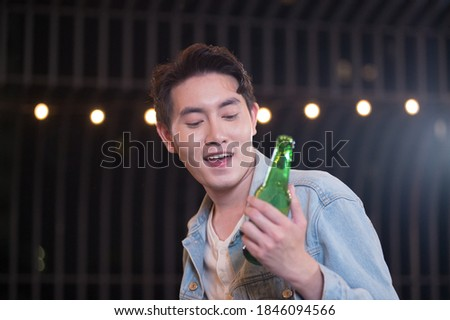 Young man holding beer bottles drinking beer drunk, Hangover