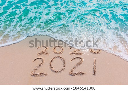 Message Year 2020 replaced by 2021 written on beach sand background. Good bye 2020 hello to 2021 happy New Year coming concept #1846141000