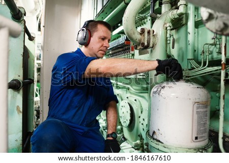 Marine engineer officer controlling vessel engines and propulsion in engine control room ECR. Ship onboard maintenance Royalty-Free Stock Photo #1846167610