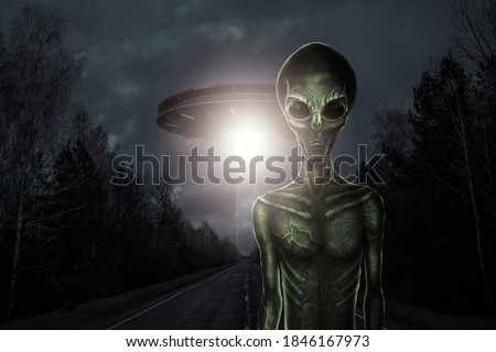 Green alien with black large glass eyes on the background of a flying saucer. UFO concept, aliens, contact with extraterrestrial civilization. Royalty-Free Stock Photo #1846167973