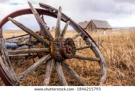 Old broken wagon wheel in farm field. Fagon wheel. Abandoned wagon wheel. Old wagon wheel is broken #1846215793