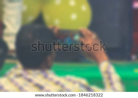 Man recording video and capturing photos during a birthday celebration and music orchestra by a smartphone.  behind a blurry foreground. Blurred image. Copy space. Pancharas jatra pala.