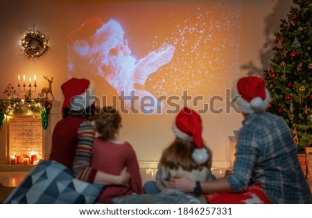 Merry Christmas and Happy New Year! People having fun near tree indoors. Loving family watching holiday movies at home. Mother, father and daughters spending time together. Royalty-Free Stock Photo #1846257331