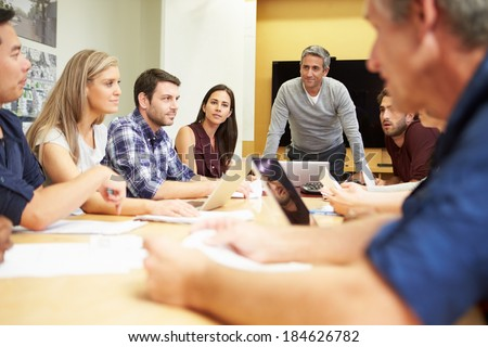 Male Boss Addressing Meeting Around Boardroom Table #184626782