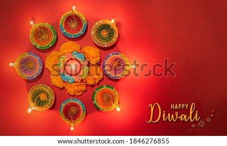 Happy Diwali - Clay Diya lamps lit during Dipavali, Hindu festival of lights celebration. Colorful traditional oil lamp diya on pink background Royalty-Free Stock Photo #1846276855