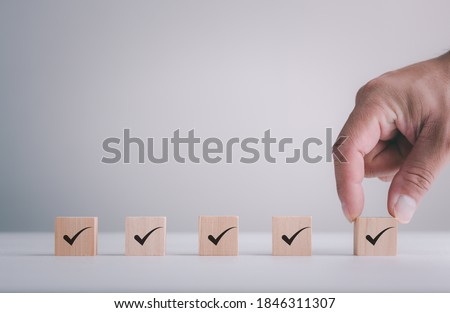 Checklist Survey and assessment concept, human hand putting cube wood with Check mark icon on wooden blocks, gray background with copy space