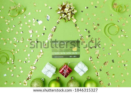 Merry Christmas. flat lay with credit card, christmas balls and christmass tree on green background.